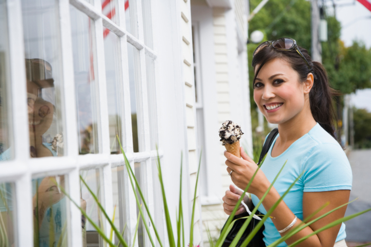 Woman holding an ice-cream cone and smiling