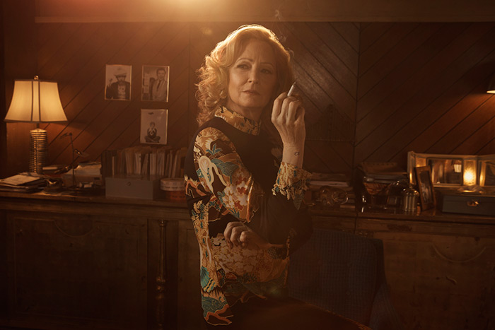 Melissa Leo as Goldie smoking a cigarette in her office