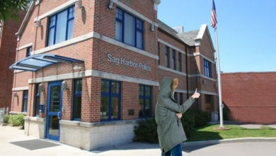 Woman in heavy winter coat doing a thumbs up outside Sag Harbor Police headquarters