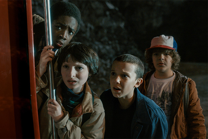The cast of Stranger Things, four kids looking scared in the dark outside