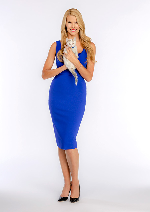Beth Stern in blue dress holding white kitten for Kitten Bowl