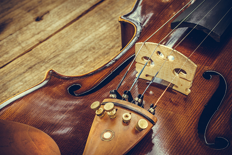 Art. Closeup of old wooden violin stringed instrument on old wooden table. Classical music.