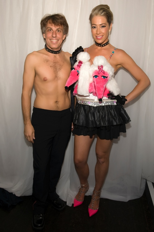"""""""Check Out These Puppies,"""" a hot pink creation by Bernadette Libardi, worn by Cheryl Lee Bennett with her escort Andrew Pilaro as they get ready to hit the runway."""