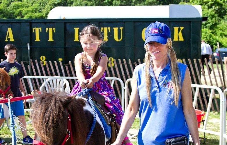 Kate Nickels, of the Little Red Barn, leads Sophie Rogoz, 4, around on Pete the horse.