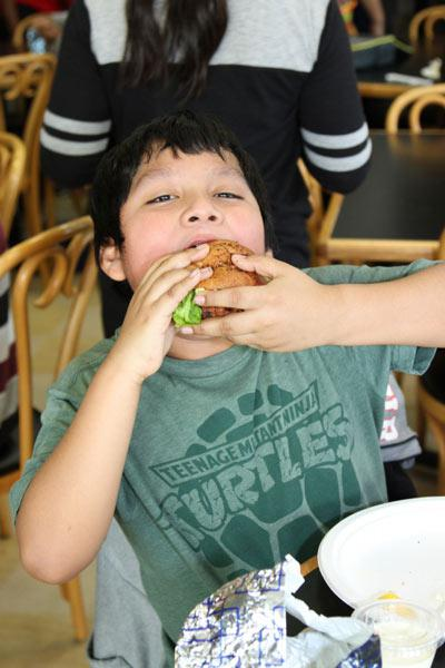 Eustorgio, age 10, takes a bite out of the delicious fish burger