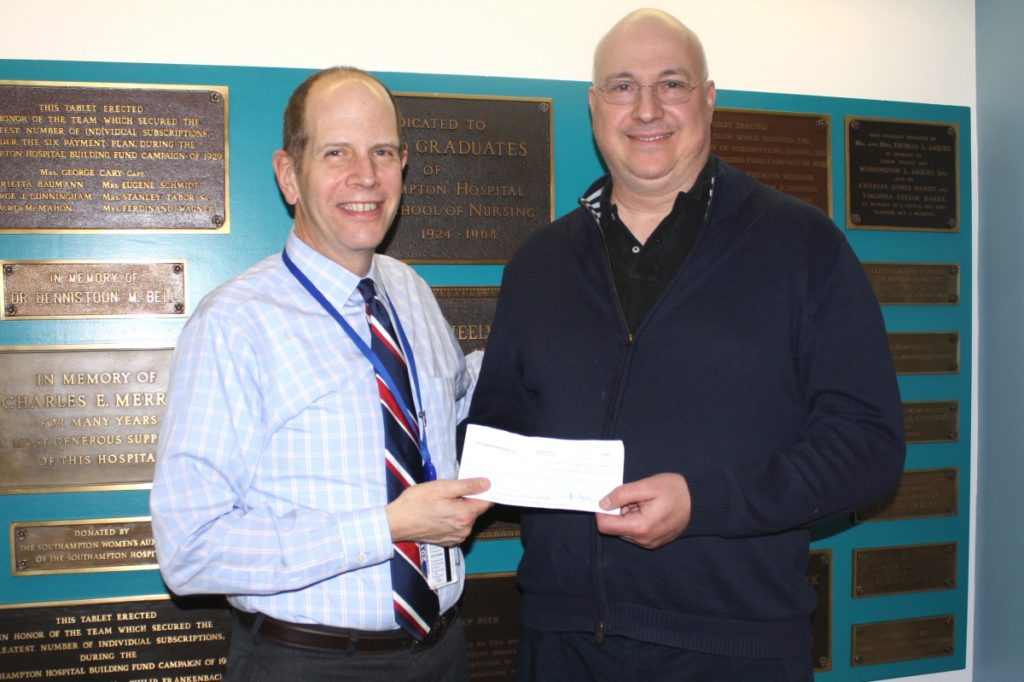 Southampton Hospital President and CEO Robert S. Chaloner accepts a check from Hamptons Health Society Chairman Peter Michalos.