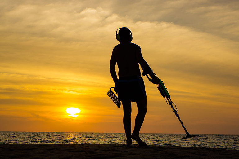 65484196 - a treasure hunter with metal detector on sunset on the beach