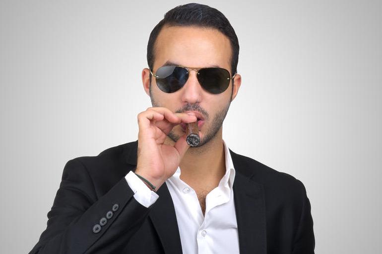 Man smoking cigar while wearing sunglasses