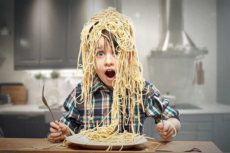 Surprised boy with pasta on the head