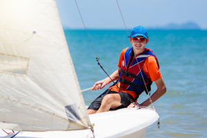 Young man sailing. Teenager boy on sea yacht. Healthy water sport. Yachting class for teen age sailor. Ocean vacation on boat. Regatta on tropical island. Beach and sail activity.