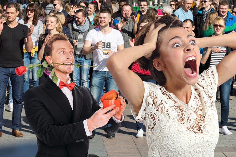 Man proposing to woman who is screaming in terror at flash mob behind them