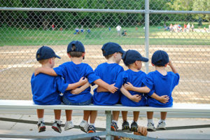 five little boys put their arms around each other before their baseball game