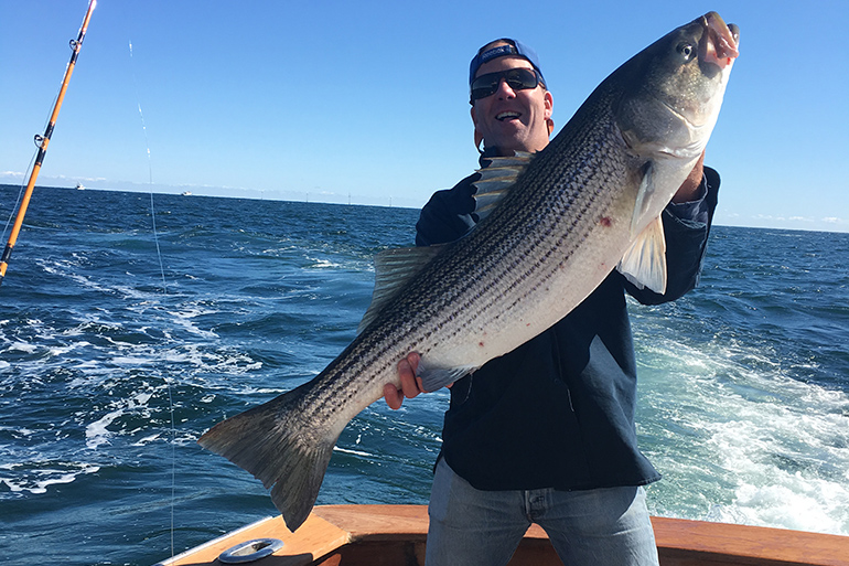 Erik Peterson with cow striped bass