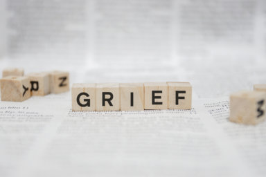 Grief Word Written In Wooden Cube - Newspaper