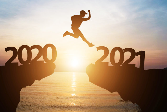 Silhouette man jump from 2020 to 2021 on cliff with sunlight for change and welcome the new year.