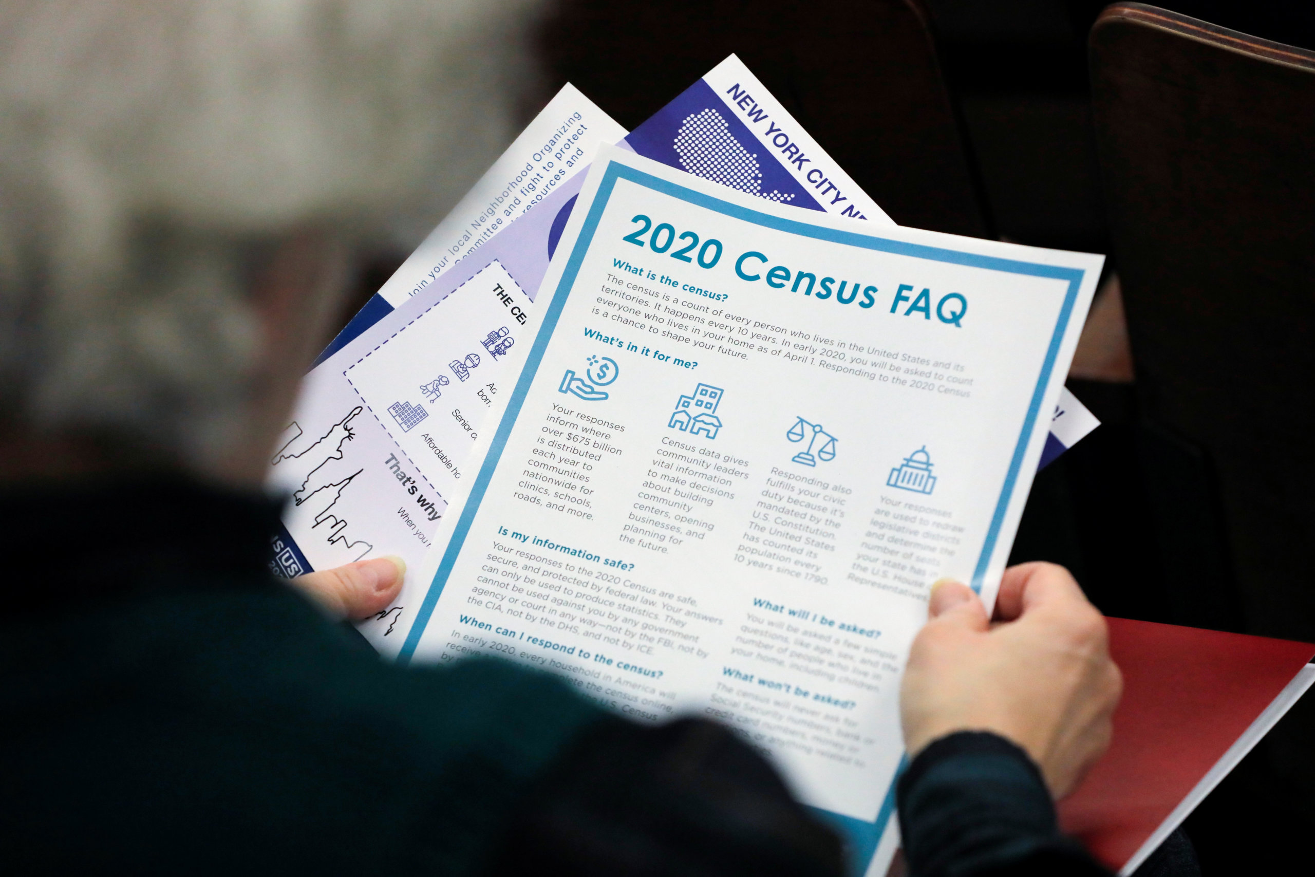 A person holds census information at an event where U.S. Rep. Alexandria Ocasio-Cortez (D-NY) spoke at a Census Town Hall at the Louis Armstrong Middle School in Queens, New York City, U.S., February 22, 2020.