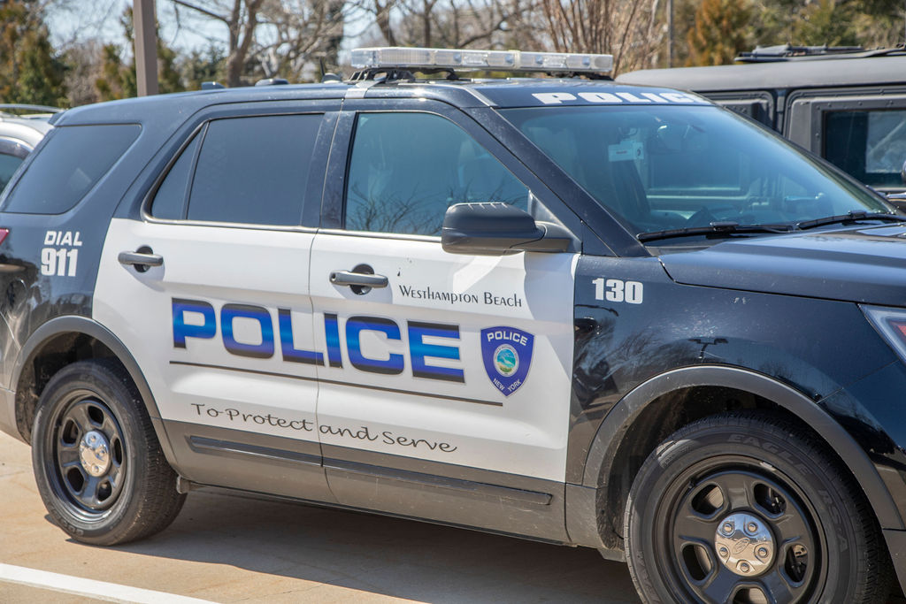 """A Westhampton Beach police car emblazoned with the department's oath """"To protect and serve"""""""
