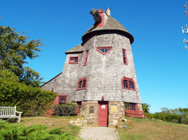 """The windmill at Stony Brook University's Southampton campus. A sign on the door reads: """"Please pardon our appearance while we build new vanes for the windmill."""""""